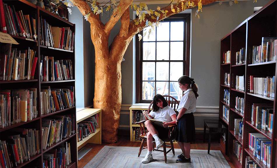 girls reading in library with tree